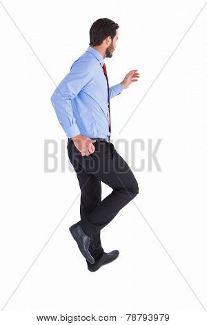 Unsmiling businessman in suit stepping on white background