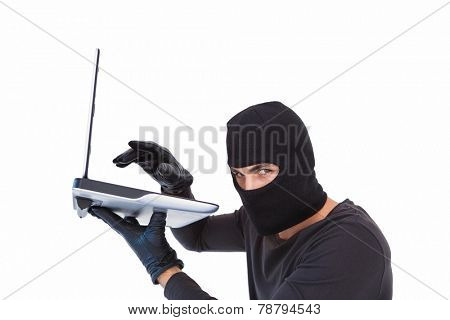 Focused burglar hacking into laptop on white background