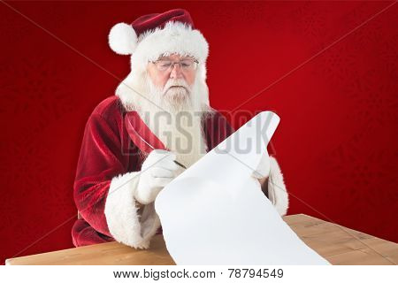 Santa writes something with a feather against red background