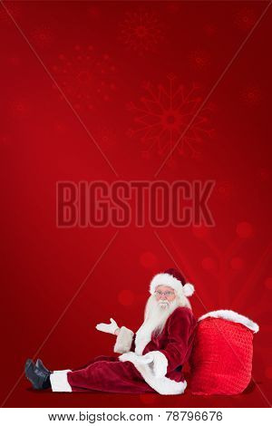 Santa sits leaned on his bag and has no clue against red background