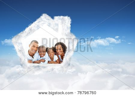 Happy family having fun lying down on bed against bright blue sky over clouds