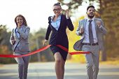 foto of competition  - Competitive businesswoman coming to finish first with her colleagues behind - JPG