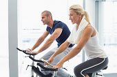 pic of gym workout  - Determined fit young couple working on exercise bikes at the gym - JPG