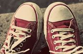 picture of dirty  - Feet in dirty red sneakers and jeans outdoors - JPG