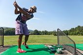 stock photo of swing  - Athletic golfer swinging at the driving range dressed in casual attire - JPG