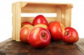 image of wooden crate  - Spilled red apples near crate on wooden table isolated on white - JPG