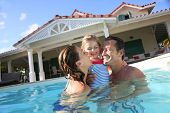 pic of 35 to 40 year olds  - Family playing in swimming pool of private villa - JPG