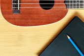 picture of bluegrass  - ukulele guitar with blank notebook and pencil - JPG