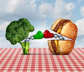 picture of battle  - Diet battle and food fight nutrition concept as a fresh healthy broccoli fighting an unhealthy cheese burger with boxing gloves punching each other - JPG