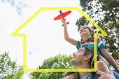 picture of aeroplan  - Boy with toy aeroplane sitting on fathers shoulders against house outline - JPG