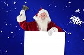 stock photo of blue-bell  - Santa holds a sign and rings his bell against blue snowflake background - JPG