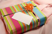 stock photo of christmas-present  - A present on pink cloth with a blank - JPG