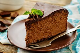 image of carbohydrate  - chocolate cheesecake with chocolate glaze on dark wood background - JPG