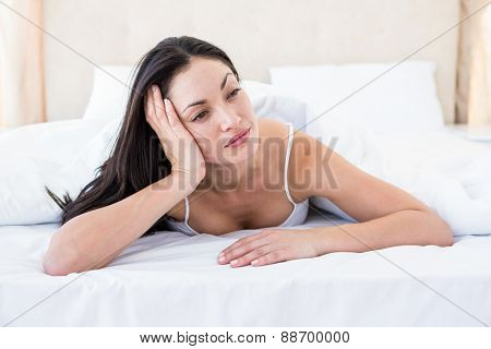 Pretty brunette thinking on bed at home