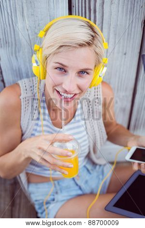 Pretty blonde woman listening music with her mobile phone and drinking orange juice on wooden background