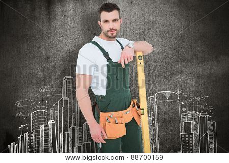 Carpenter smiling to camera with spirit level against hand drawn city plan