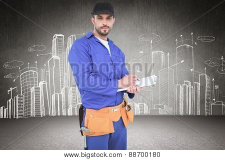 Handyman in blue overall writing on clipboard against hand drawn city plan