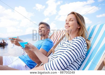 Young man and woman with martini relaxing at summer resort