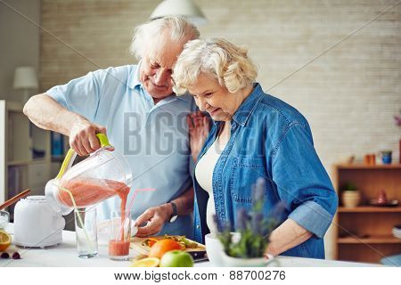 Senior man pouring fruit smoothie into glass with his wife near by