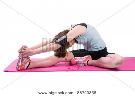 Pretty brunette stretching her leg on exercise mat on white background
