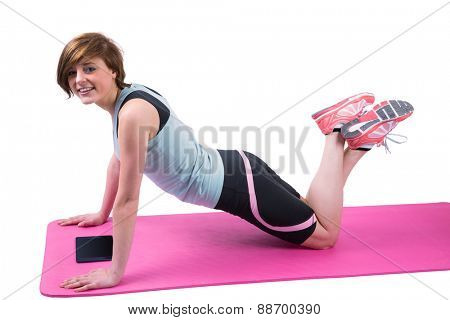 Pretty brunette looking at camera and doing press up on fitness mat on white background
