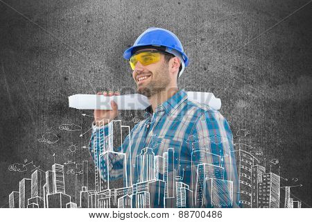 Smiling architect looking away while holding blueprint against blackboard