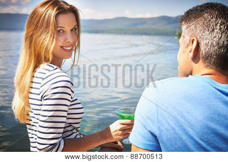 Pretty girl with cocktail looking at camera with young man near by