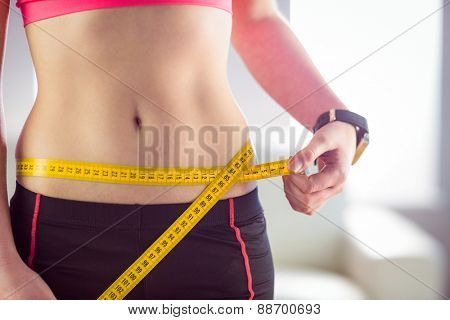 Slim woman measuring waist with tape measure at home in the living-room