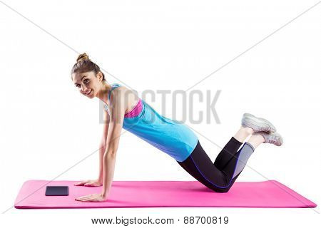 Fit woman doing press up on mat on white background