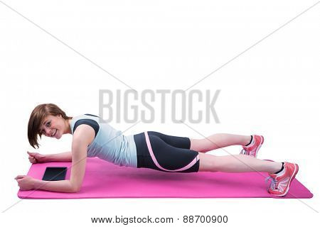 Pretty brunette doing plank on fitness mat on white background