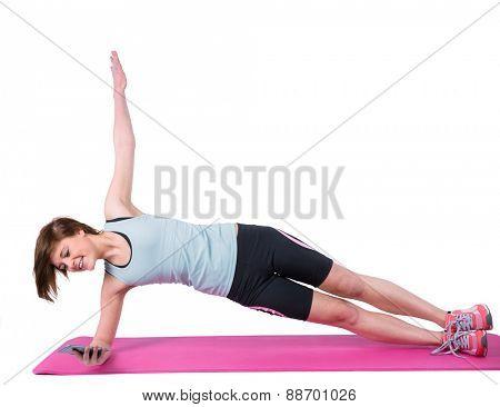 Pretty brunette doing side plank on exercise mat on white background