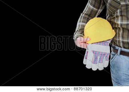 Manual worker holding helmet and gloves against black