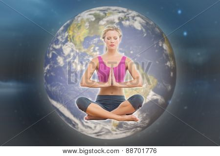 Calm blonde sitting in lotus pose with hands together against stars twinkling in night sky