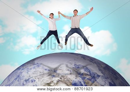Couple jumping and holding hands against blue sky