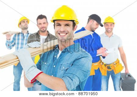 Composite image of happy carpenter carrying wooden planks