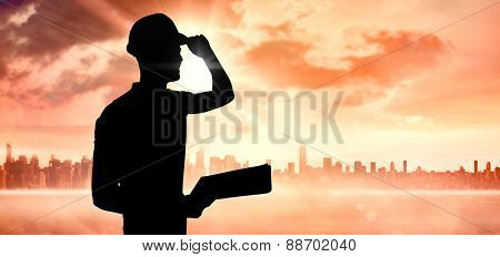 Manual worker wearing hardhat while holding clipboard against sun shining over city