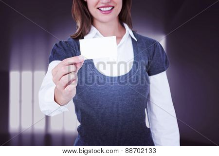 Smiling woman showing card against abstract room