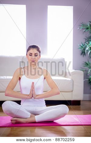 Fit woman doing yoga on mat at home in the living room