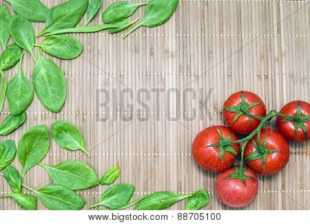 Spinach Leaves And Branch Of Ripe Tomatoes On A Bamboo Mat