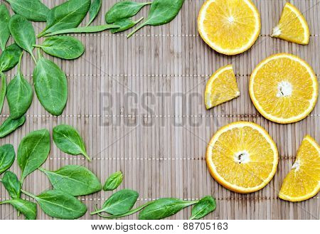 Spinach Leaves And Orange Slices On A Bamboo Mat