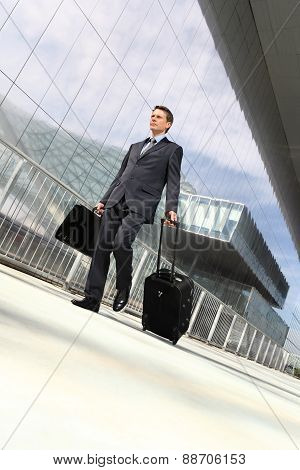 businessman walking with suitcase and trolley, travel concept