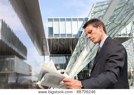 business man reading the financial newspaper, between the buildings of glass