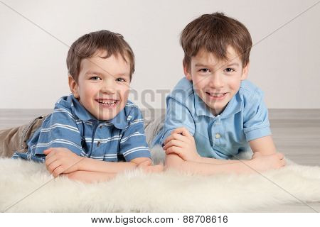 Elder And Younger Brother Sitting On Pufe
