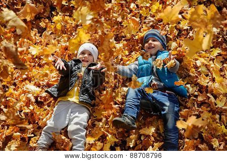 Happy children in autumn park lying on leaves