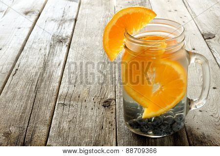 Water with oranges and blueberries against wood