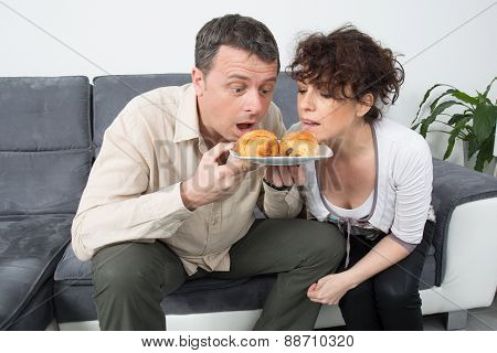 Couple Sit On Grey Couch Together Eating Croissant