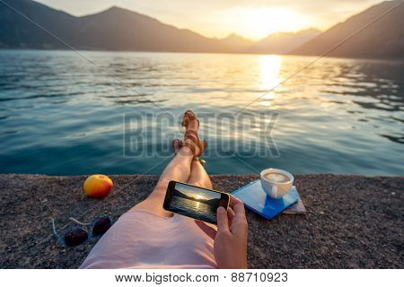 Woman holding phone lying on the pier