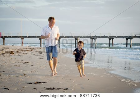 Happy Father Playing On The Beach With Little Son Running Excited With Barefoot In Sand And Water