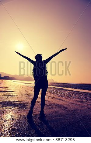 cheering young woman hiker open arms on sunrise beach