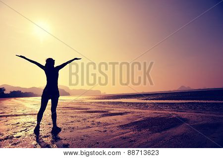 cheering young woman open arms on sunrise beach